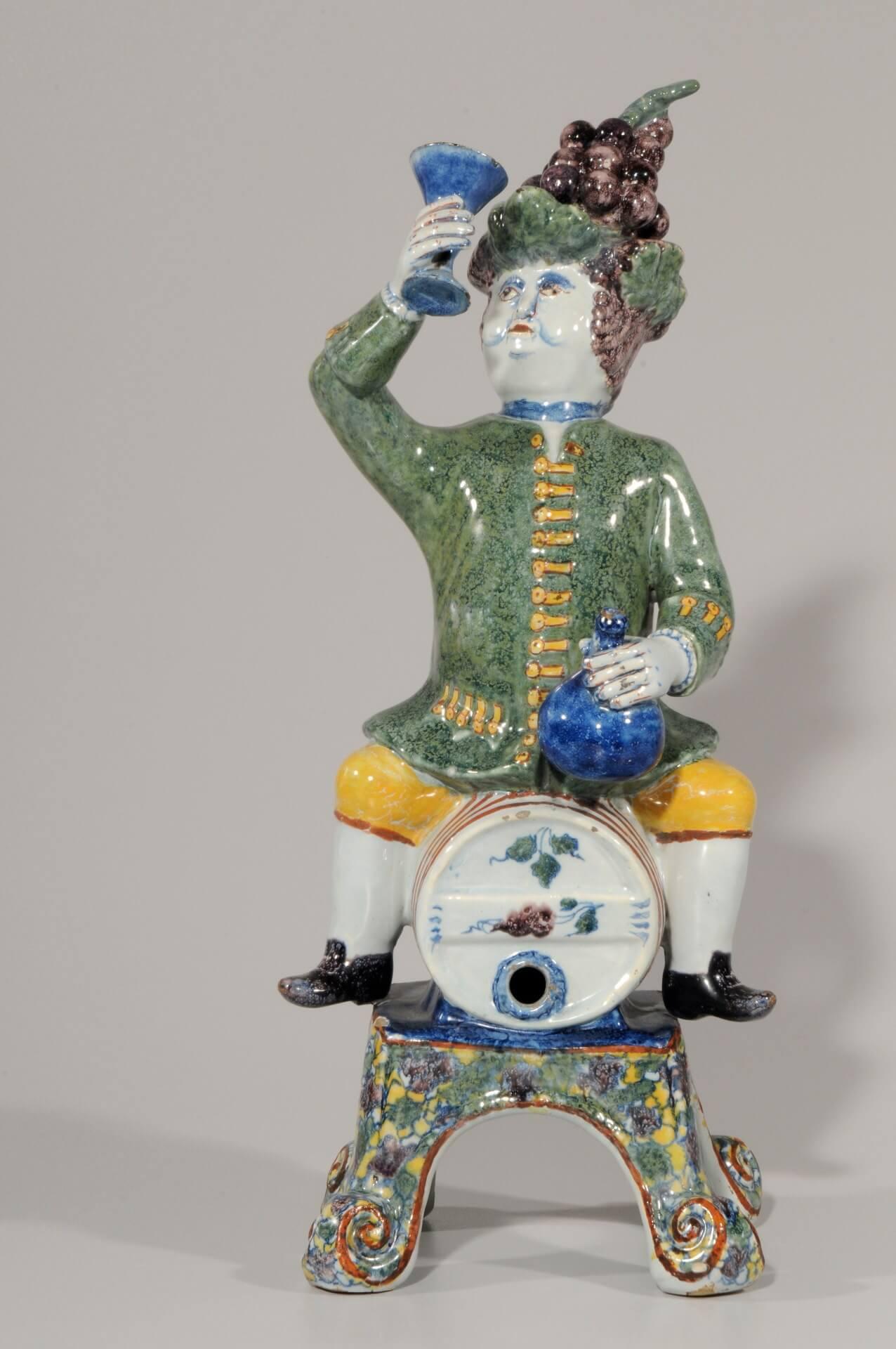 Aronson Antiquairs old antique polychrome figurine of man sitting on barrel