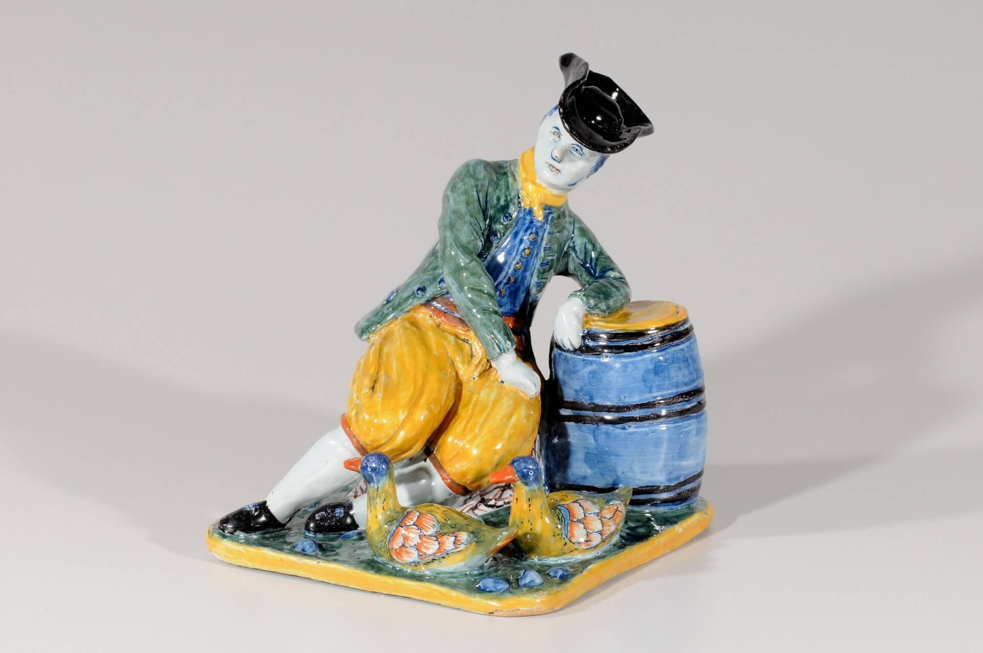 Antique polychrome figurine of man hanging on barrel