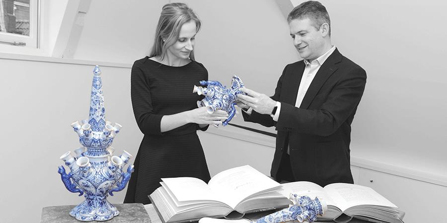 Aronson Antiquairs Celine Ariaans and Robert Aronson discussing Delftware tulipvases